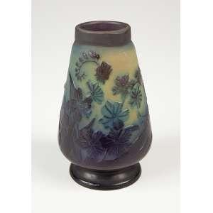 GALLÉ, Emile<br />Vaso de vidro artístico, cônico, decoração floral em tons de verde e azul. 13 cm de altura. <br />Assinado. França, séc. XX.