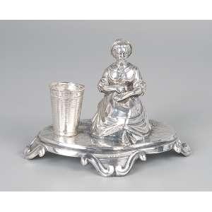 Paliteiro de prata repuxada e cinzelada, dama sentada ao lado de balaio. 10 cm de altura. <br />Marca do teor 800. Itália, séc. XX.