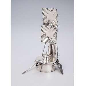 Rara lamparina portuguesa de prata repuxada, constituída por reservatório para querosene com bico lateral para o pavio, duas placas refletoras móveis e três apetrechos. 16 cm de altura. Contraste do Porto, em uso 1887 e 1938.