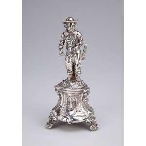 Paliteiro de prata portuguesa repuxada e cinzelada figura de pastor sobre pedestal com cabeças de cães. 22 cm de altura. Portugal, 1900 até 1913.