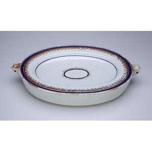 Travessa de porcelana Cia das Índias, ovalada, borda com filete azul e elementos repetitivos em douração. Dois orifícios nas laterais para introdução de água quente. 36,5 x 24,5 cm. China. Qing Qianlong (1736-1795).