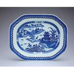 Travessa de porcelana Cia das Índias, azul e branca, borda recortada e ornada por barrados repetitivos. No plano, paisagem lacustre com pagodes. 40 x 32 cm. China, séc. XVIII.