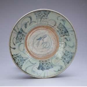 Medalhão de porcelana azul e branca, circular, com pequenos recortes na orla, aba ornamentada com barrado de elementos repetitivos e florão no centro da caldeira. Sob a aba rosácea e elementos decorativos. 32,5 cm de diâmetro. China, Dinastia Ming, (1368-1644).