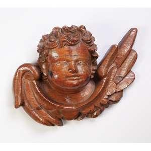 Cabeça de anjo esculpida em carvalho e encerada. 35 x 12 x 35 cm de altura. Europa, séc. XVIII / XIX.