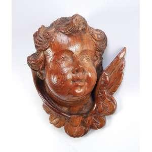 Cabeça de anjo esculpida em carvalho e encerada. 21 x 13 x 26 cm de altura. Europa, séc. XVIII / XIX.