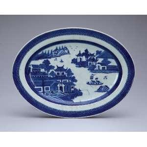 Travessa de porcelana azul e branca. Cia das Índias, ovalada, decoração Macau, aba com barrado em treliça, plano com lago e pagodes. 30 x 22,5 cm. China. Qing Jiaqing (1796-1820).