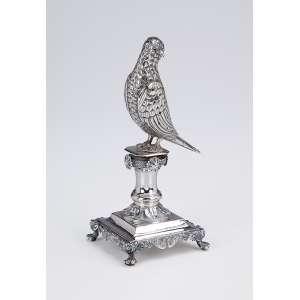 Paliteiro de prata portuguesa repuxada, fundida e cinzelada. Pássaro sobre pedestal. Base quadrangular e quatro pés em garra. 15 cm de altura. Contrastes prejudicados na leitura.