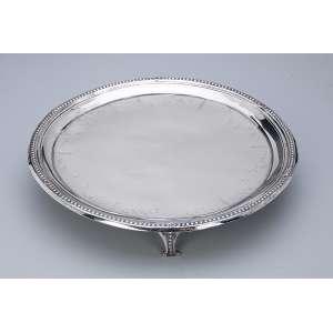 Salva de prata repuxada. D. Maria I, circular, borda em perolados, sobre 3 pés vazados. 25,5 cm de diâmetro. Contrastes prejudicados na leitura. Séc. XIX.