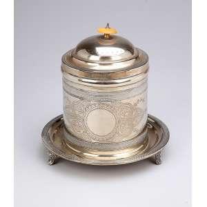 Caixa para chá de metal prateado, circular, pega da tampa em marfim. 20 cm de altura. Europa, séc. XIX.