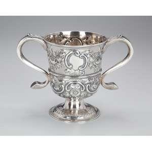 Rara e importante taça de prata inglesa, repuxada e cinzelada, decoração floral, com duas alças laterais. 13 cm de diâmetro x 16,5 cm de altura. Contraste de Newcastle para 1758 e do prateiro John Langlands.