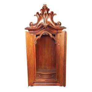 Oratório de madeira lavrada com duas portas frontais almofadadas e encimado por florão de inspiração barroca. 68 x 33 x 145 cm de altura. Brasil, séc. XIX.
