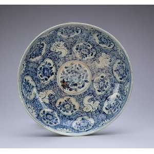 Medalhão de porcelana chinesa azul e branca, circular, ornamentado na caldeira com pequenas reservas recortadas em volta de uma central circular contendo flores, sobre fundo de padrão decorativo. Sob a aba largo barrado de elementos vegetais estilizados. 32,7 cm de diâmetro. Dinastia Ming (1368-1644).
