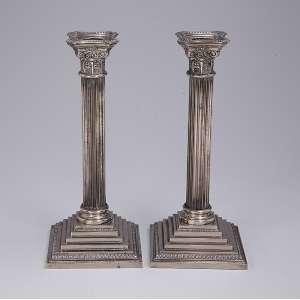 Par de castiçais de metal prateado inglês, base quadricular, fuste canelado e capitel coríntio. 30 cm de altura. Séc. XX.