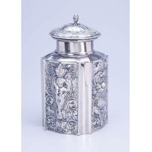 Caixa para chá de metal prateado, repuxado e cinzelado, decorada com cupidos e ânforas em relevo. 17 cm de altura. Europa, séc. XX.