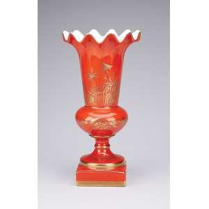 Vaso de porcelana rouge-de-fér decorado com cenas em douração, bocal drapeado, base quadrangular. 25,5 cm de altura. Marca de manufatura sob a base. Europa, séc. XX.