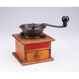 Antigo moedor de café de bronze, acoplado em caixa de madeira com gavetinha frontal. Marca do fabricante Parker's Eagle Coffe Mile. 15 x 15 x 20 cm de altura. U.S.A, séc. XX.
