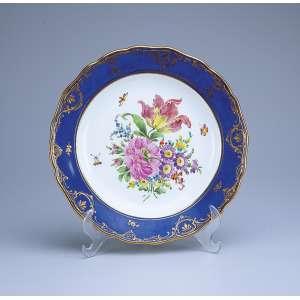 Prato de porcelana, borda azul cobalto e plano com flores. 25 cm de diâmetro. Marca da manufatura de Meissen. Séc. XX.