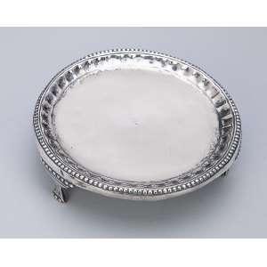 Mini salva de prata repuxada, circular, com borda perolada ao estilo D. Maria I. Sobre três pés. 10 cm de diâmetro. Brasil, séc. XIX.
