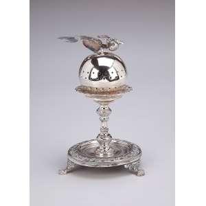 Paliteiro de prata repuxada e cinzelada, pássaro sobre esfera. Base circular fenestrada sobre 3 pés em garra. 15 cm de altura. Contrastes prejudicados na leitura. Brasil ou Portugal, séc. XIX.