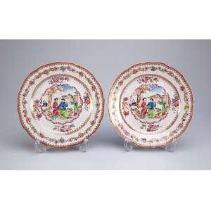 Par de pratos rasos de porcelana Cia das Índias, borda recortada e ornada por flores, <br />na caldeira cena romântica no jardim. 23 cm de diâmetro. China, séc. XVIII.