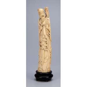 Escultura de marfim, ancião com peixes e feixe de galhos, sobre base de madeira. <br />36 cm de altura. Assinado Japão, séc. XIX.