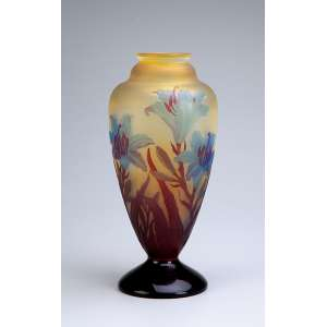 Vaso de vidro artístico de Gallé, decorado com flores de hibisco em tons azul e marrom <br />sobre fundo amarelado. Assinado. 25 cm de altura. França, séc. XX.