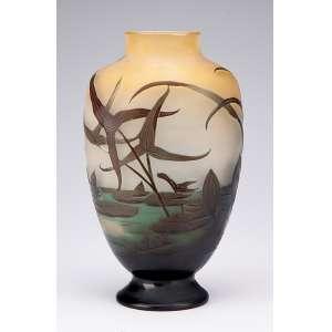 GALLÉ. Vaso de vidro artístico, formato ovalado e achatado, decorado com arbustos e flores <br />lacustres em tons de verde sobre fundo amarelado. 23 cm de altura. Assinado França, séc. XX.