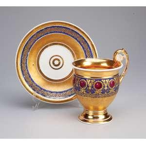 Xícara com pires de porcelana francesa, sem marcas, decoração em barrados azuis, <br />perolados bordeaux e frisos dourados. Circa 1830.