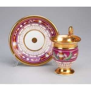 Xícara com pires de porcelana não identificada. Barrado bordeaux com <br />ânfora e objetos em policromia. Circa 1850.