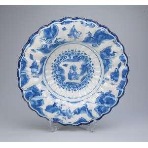 Medalhão de faiança azul e branco, borda em gomos com pequenos desgastes. <br />34,5 cm de diâmetro. Portugal, séc. XIX.