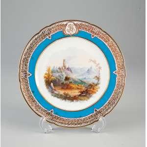 Prato raso de porcelana Vieux Paris, borda com renda dourada envolvendo faixa azul com <br />cartela com o monograma. F.J.G. 22,5 cm de diâmetro. França, séc. XIX.