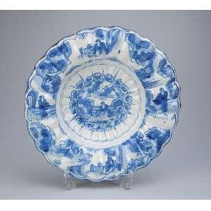 Medalhão de faiança azul e branca, borda em pequenos gomos, ao centro pintura de <br />inspiração chinesa. 33 cm de diâmetro. Portugal, séc. XIX.