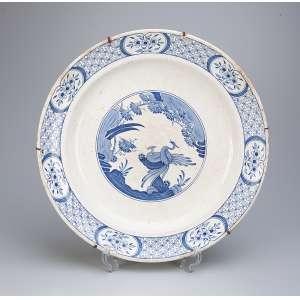 Medalhão de louça inglesa, azul e branca, borda em treliças e flores, ao centro pintura <br />de inspiração chinesa. 37 cm de diâmetro. Marca da manufatura Old Chelsea. Séc. XIX.