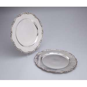 Par de pratos de prata repuxada e cinzelada, circulares, borda recortada. <br />28 cm de diâmetro. Marca do teor 900. Europa, séc. XX.