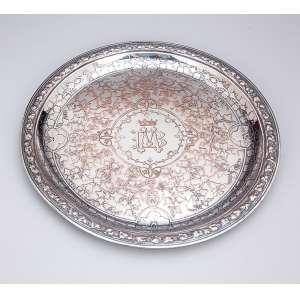 Prato de metal prateado de Christofle, circular, decorada com hibiscos em relevo. Apresenta <br />ao centro monograma M.B coroado. 27 cm de diâmetro. França, séc. XIX. (necessita banho de prata).