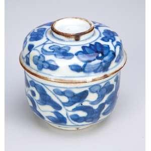 Pequeno bowl com tampa, de porcelana azul e branca, decoração floral. <br />7,5 cm de diâmetro x 7 cm de altura. China, Qing Kangxi (1662-1722). <br />O Brasil e a Cerâmica Antiga, de E. F. Brancante, pág. 296.