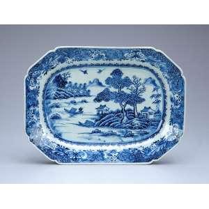 Travessa de porcelana azul e branca, Cia das Índias, retangular e recortada, aba com borboletas <br />e flores, no plano paisagem lacustre com edificações. 28,5 x 21 cm. China. Qing Qialong (1736-1795).