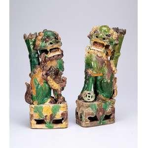 Casal de cães de fó, de cerâmica vitrificada em tons de verde, amarelo e aubergine, usados como porta <br />varetas de incenso. O macho com a pata sobre esfera (como se fosse o mundo), e a fêmea conduz a <br />cria pelas costas. 22 cm de altura. China, dinastia Qing, período Kangxi (1662-1722).