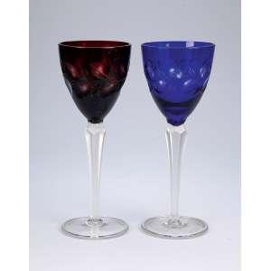 Duas taças de cristal de pé alto, sendo uma na cor vinho e outra azul, ambas lapidadas. <br />22,5 cm de altura. Europa, séc. XX.
