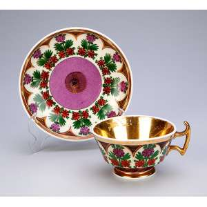 Xícara e pires de porcelana, decoração floral policrômica com barrado dourado.