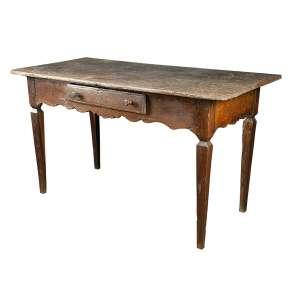 Mesa rústica, estilo colonial brasileiro, tampo retangular sobre caixa com uma gaveta, saia recortada. <br />142 x 67 x 80 cm de altura. Brasil, séc. XIX.