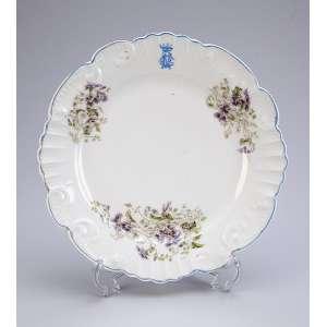 Prato raso de porcelana, circular, borda recortada e decoração floral. Apresenta monograma NC coroado. <br />23,5 cm de diâmetro. França, séc. XX.