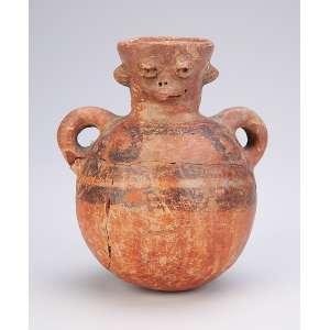 Pequeno jarro de barro pré-colombiano, com duas alças laterais e bocal com figura mitológica. <br />13 cm de altura. (totalmente colado).