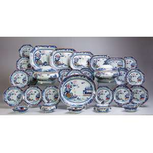 Serviço de porcelana Cia das Índias, decorado em azul cobalto e esmaltes policromados com paisagens e flores, constituído de: duas sopeiras, cinco travessas retangulares, a maior com 42 x 32,5 cm, uma travessa ovalada, 40,5 x 34,5 cm, uma terrina oval para molho com présentoir, uma terrina retangular para molho, três molheiras, 17 pratos rasos e seis pratos fundos, totalizando 37 peças. China, Qing Qianlong. (1736-1795).
