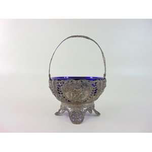 Elegante cesta de fina prata de lei ricamente trabalhada em fenestrado interior em cristal azul cobalto contraste lua e coroa .Alemanha Séc XIX/XX. 11 cm de alt e 16 de diâm.
