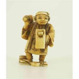 Netsuke em marfim japonês composto de um marceneiro, assinado na base. 5 cm de alt.