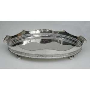 Centro de mesa em prata de lei,ovalado,borda recortada, com alças e sobre 4 pés arredondados. altura 14cm, largura 51cm e 83 cm de comprimento.