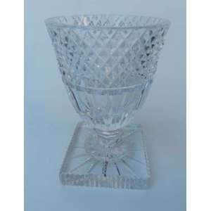 Pequeno vaso de cristal, lapidação bico de jaca na borda, tendo a base quadrada com estrela ao centro medindo 9 cm por 9 cm e15 cm de altura.Apresenta lasca no alto da borda.