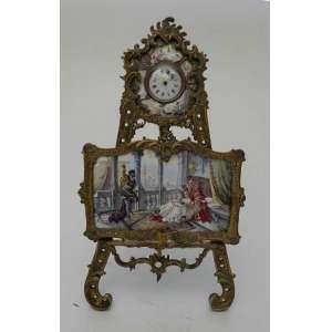 Cavalete de bronze dourado, tendo um relógio no alto, com pintura em esmalte ao redor, sustentando um quadro com cena palaciana também pintado em esmalte.Apresenta pequenos danos na pintura.Itália, meados do sec.XX. Alt.20cm