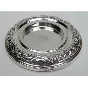 Descanso de mesa para garrafas ou jarras, de prata de lei inglesa, decorada na borda,medindo 18 cm. de diametro e 3 cm de altura.